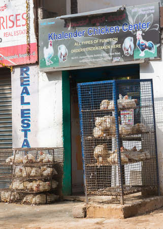 BENGALURU, INDIA - CIRCA NOVEMBER 2013  Butcher shop with racks of cages holding living chickens