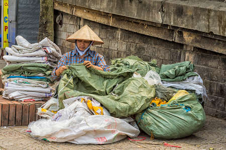HANOI, VIETNAM - CIRCA MARCH 2012: Woman repairs old plastic bags in the street of Hanoi. Recycling and reusing green and white garbage sacks. Editorial