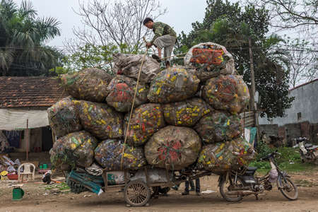 voluminous: HANOI, VIETNAM - CIRCA MARCH 2012: Recycling cans and bottles loaded on cart behind motorbike. Voluminous colorful and amazing proposition.