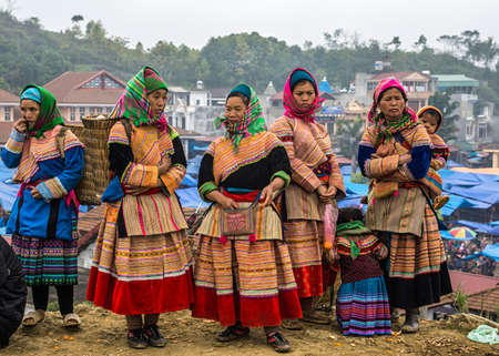 sunday market: BAC HA, VIETNAM - CIRCA MARCH 2012: Hmong women in traditional dress on Sunday market wait and chat.
