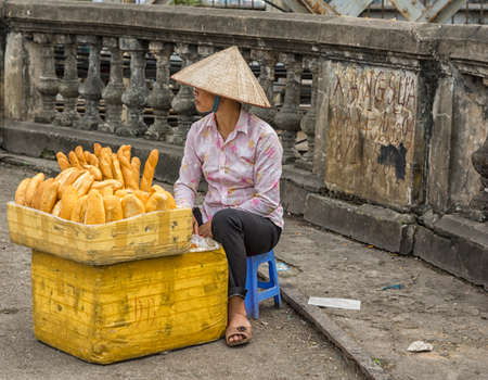 HANOI, VIETNAM - CIRCA MARCH 2012: Young woman selling fresh baked bread in the street. On the on-ramp of Long Bien Bridge.