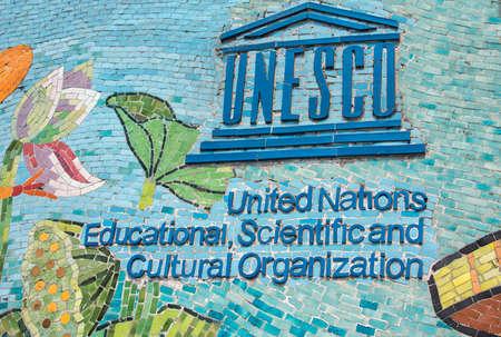 HANOI, VIETNAM - CIRCA maart 2012: UNESCO-logo op de langste mozaïek muur in de wereld. Blauwe logo en naam op kleurrijke fresco.