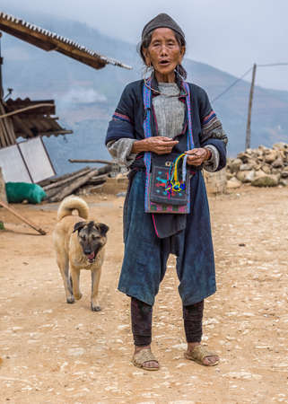 spunky: TA VAN, VIETNAM - CIRCA MARCH 2-12  Hmong village elder and dog selling souvenirs on the road