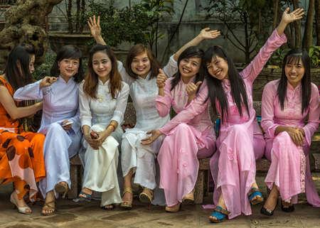 HANOI, VIETNAM - CIRCA MARCH 2012: Seven joyful female university seniors dressed in Ao Dai. Happy smiles and positive waves at Temple of Literature.