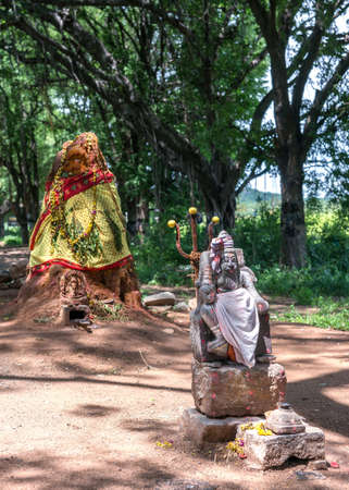 "Old ant-hill converted into shrine for Manasa, the snake-goddess  The man with the trident is known as ""Karuppannaswamy "" He is a demi-god servant of Manasa and the protector of the shrine"