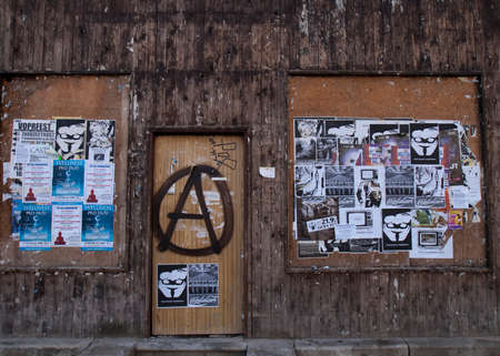 anarchist: PLZEN, CZECH REPUBLIC - CIRCA SEPTEMBER 2010  A business with dark filthy wooden walls is completely boarded up  Anarchist have painted their classic encircled A-logo on the door, and have glued anti-capitalist posters near by  Capitatlism is written in t