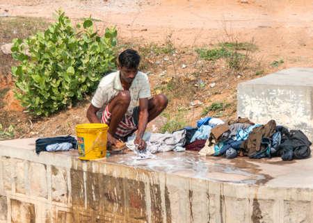 khajuraho: India Khajuraho - 24 de febrero 2011 - El hombre lavar la ropa de forma manual en la losa de hormig�n del puente del r�o