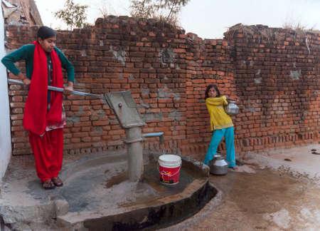 bomba de agua: India Khajuraho - febrero 2011 Muchachas de los pares de bombeo de los últimos ollas de agua de la bomba comunal en la noche Editorial