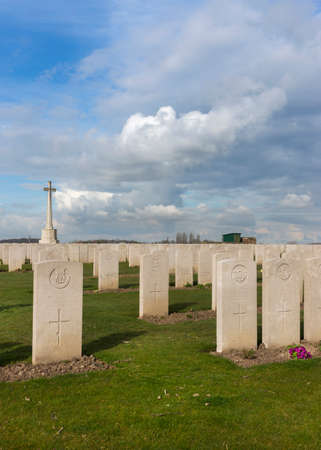 IEPER, BELGIUM - CIRCA MARCH 2014: Belfry of Ypres (Ieper) with Flanders Fields Museum. Tomb stones and the cross at Bard Cottage Cemetery at Ypres, Flanders, Belgium. Portrait.