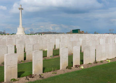 IEPER, BELGIUM - CIRCA MARCH 2014: Belfry of Ypres (Ieper) with Flanders Fields Museum. Tomb stones and the cross at Bard Cottage Cemetery at Ypres, Flanders, Belgium. Editorial