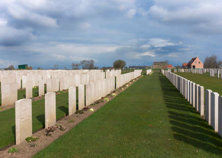 IEPER, BELGIUM - CIRCA MARCH 2014: Belfry of Ypres (Ieper) with Flanders Fields Museum. Rows of tombs at Bard Cottage Cemetery in Ypres, Flanders, Belgium - Landscape. Editorial