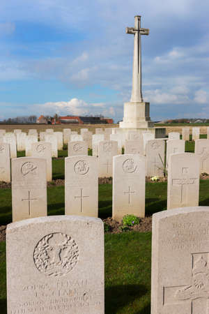 IEPER, BELGIUM - CIRCA MARCH 2014: Belfry of Ypres (Ieper) with Flanders Fields Museum. Tomb stones and the cross at Bard Cottage Cemetery at Ypres, Flanders, Belgium.