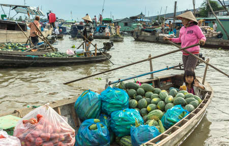 CAN THO, VIETNAM - CIRCA APRIL 2012: Mother and daughter loaded their boat with water melons and bell peppers. At the floating market on the Hau River.