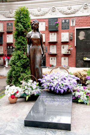 MOSCOW, RUSSIA - CIRCA SEPTEMBER, 2010: Last resting place of Raisa Gorbachev-Titarenko at the Novodevichy National cemetery in Moscow. Black tomb slab in front of baskets of white and blue flowers with the bronze, life sized, statue of a mourning young w