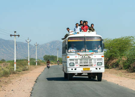 RAJASTHAN, INDIA - CIRCA FEBRUARY 2011: Public transport bus with plenty of passengers on the roof driving on the road.