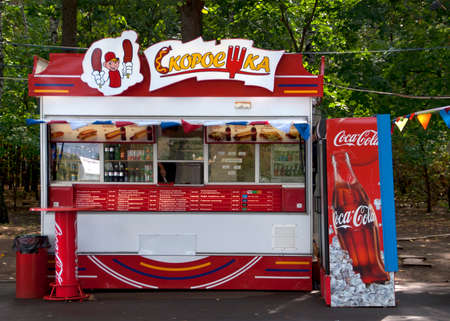 MOSCOW, RUSSIA - CIRCA SEPTEMBER 2010: Fast food booth with Coca Cola advertisements. Red and white are the dominant colors of this modern and efficient looking fast food stand along the side of a park in Moscow. Sajtókép