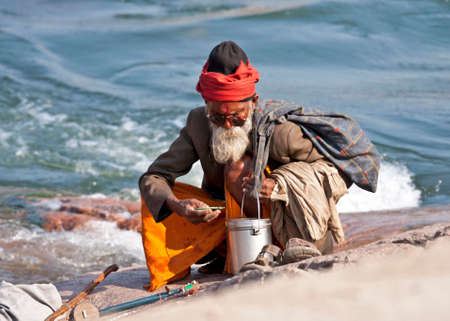 ORCHHA, INDIA - CIRCA FEBRUARY 2011: White bearded old man, a sadhu or holy man, with sunglasses and the classic metal water pot sits on his haunches at the rocky rivers edge.