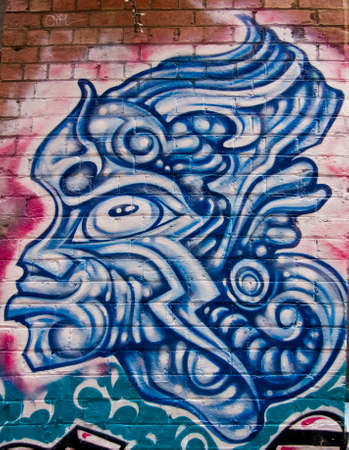 MELBOURNE, AUSTRALIA - CIRCA NOVEMBER 2009  Colorful graffiti in back alley of downtown, depicts a fierce looking, blue, all-lined male mask