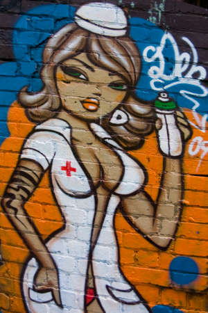 wooing: MELBOURNE, AUSTRALIA - CIRCA NOVEMBER 2009  Colorful graffiti in back alley of downtown, depicts a sexy, wooing female nurse with green eyes, brown hair and white outfit  Editorial