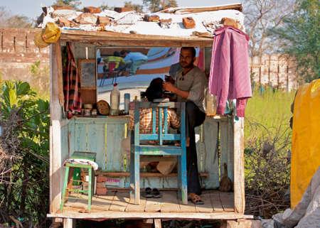 ORCHHA, INDIA - CIRCA februari 2011 Standing in een houten hokje, baring staat om rechtop te staan, een kapper is het geven van een klant een kapsel De kast staat op stelten, zit aan de kant van de weg, en de stenen houden een zeil aan het dekken dak