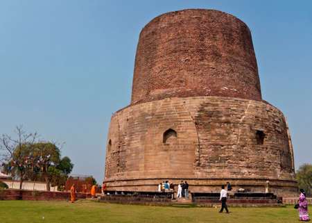 sarnath: SARNATH, INDIA - CIRCA FEBRUARY 2011  Dhamekh Stupa is a Buddhism historic site, considered the birthplace of Buddhism, since the Buddha gave his first lecture here  Huge tall red brown solid tower of stones and bricks against a blue sky, with pilgrims wa Editorial