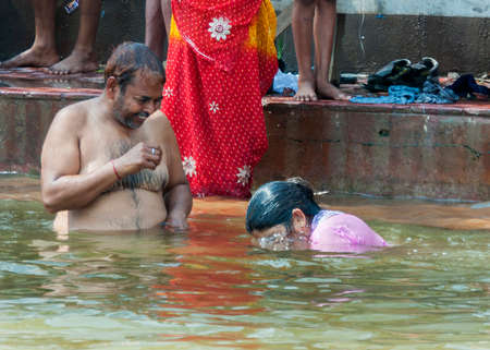 BITHOOR, INDIA - CIRCA MARCH 2011  Husband and wife having fun during ritual bathing in the Ganges River
