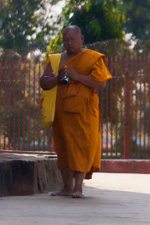 sarnath: VARANASI, INDIA - CIRCA FEBRUARY 2011  Buddhist monk in orange robe circles the Dhamekh Stupa
