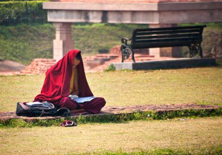 sarnath: SARNATH, INDIA - CIRCA FEBRUARY 2011  Young monk with his head partly and his body covered by a red sheet of cloth, sitting cross legged on the ruin of a wall, reads papers