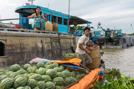 can tho: CAN THO, VIETNAM - CIRCA APRIL 2012  Retailer with water melons meets wholesaler at Cai Rang floating market  Small retailer sloops moves along larger wholesaler barge