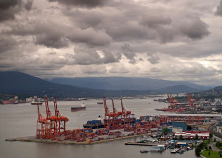 VANCOUVER, CANADA - CIRCA JULY 2011  Wide shot over a large part of Vancouver harbor with container terminal in the foreground  Extremely dark, cloudy, stormy skies