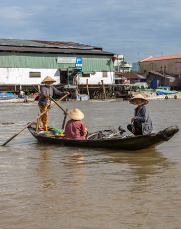 can tho: CAN THO, VIETNAM - CIRCA APRIL 2012  Woman ferries two other women in her small rowboat over the Hau River Background on the shore is an industrial building  Editorial