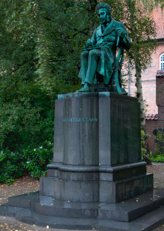existentialism: COPENHAGEN, DENMARK - CIRCA SEPTEMBER 2010: Statue of Soren Kierkegaard turned green and hidden in the green of a park. He is the first existentialist philosopher and 19th century poet and author.