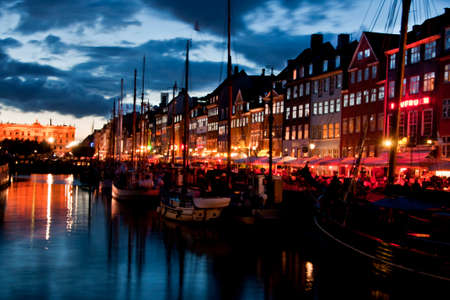 COPENHAGEN, DENMARK - CIRCA SEPTEMBER 2010: The most colorful side of Nyhavn with restaurant row and the sloops in the water at night fall.