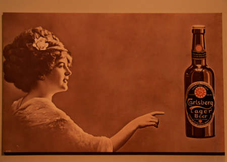 carlsberg: COPENHAGEN, DENMARK - CIRCA SEPTEMBER 2010: Old sepia poster promotes Carlsberg Lager beer, and features a female beauty of earlier times.