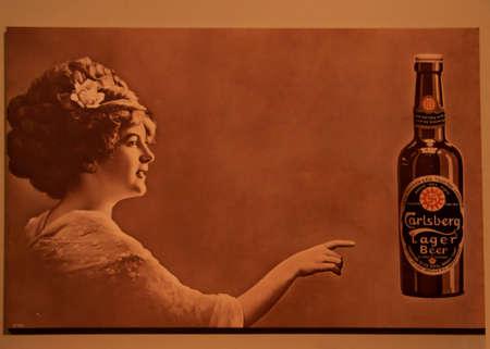 promotes: COPENHAGUE, Dinamarca - alrededor de septiembre de 2010: cartel sepia Antiguo promueve la cerveza Carlsberg Lager, y cuenta con una belleza femenina de �pocas anteriores. Editorial