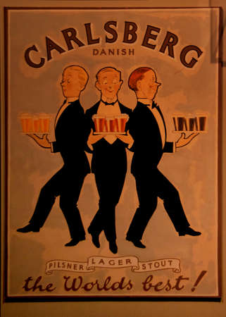 carlsberg: COPENHAGEN, DENMARK - CIRCA SEPTEMBER 2010: Old poster promotes the pilsner, the lager and the stout brewed by the Carlsberg brewery in town. It features three male servants, each with a tray of the specific beers.