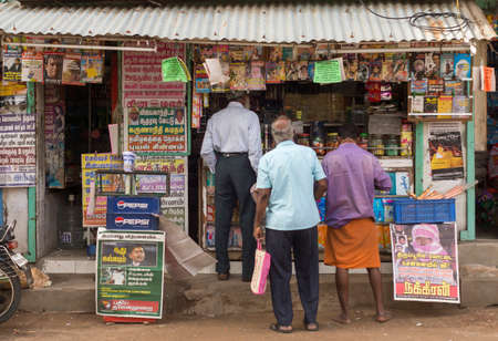 THIRUVANNAMALAI, INDIA - CIRCA OCTOBER 2013: Newspapers and Magazines for sale at small street shop. The dominant language in print is Tamil. Three locals line up to buy.