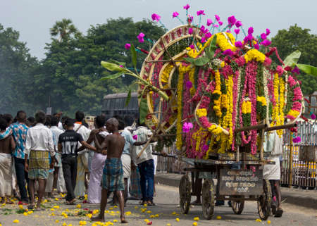 GINGEE, INDIA - CIRCA OCTOBER 2013: A funeral procession with only male participants proceeds through the streets of Gingee. The deceased man is exposed on a pushcart covered with flowers. Editorial