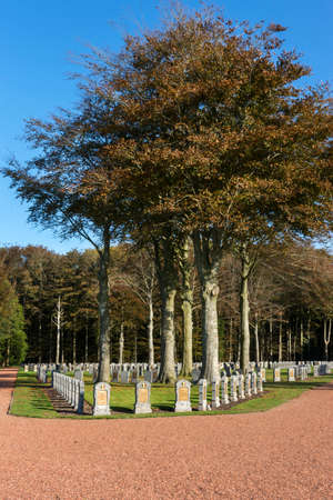 HOUTHULST, BELGIUM - OCTOBER 27, 2014: Lines of tombstones under trees covered in fall colors for the soldiers who fell during the last major attack of the war against the Germans.
