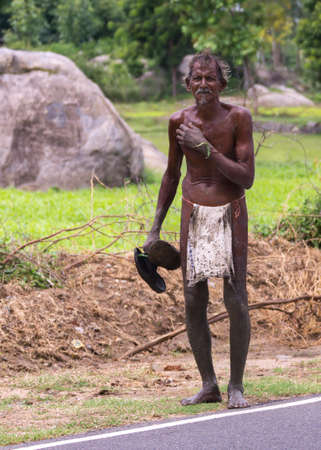 destitute: KUMBAKONAM, INDIA - OCTOBER 10, 2013: A dark-skinned Tamil man walks along the road wearing just a filthy loin-cloth. Editorial