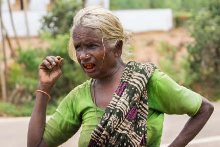 KUMBAKONAM, INDIA - OCTOBER 10, 2013: Close-up of an old female farmer with gray hair and her mouth full of red, bad teeth and a red tongue, because she chews betel leaves.