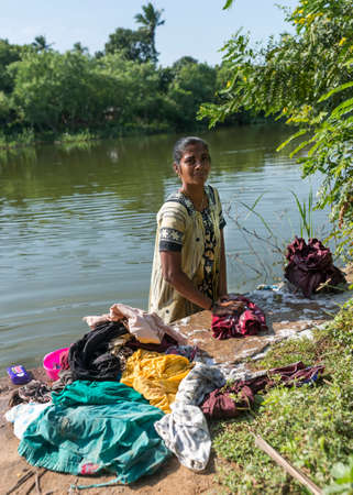KUMBAKONAM, INDIA - OCTOBER 11, 2013: A young woman stands in the river doing the laundry by scrubbing the clothes on rocks and using lots of soap.