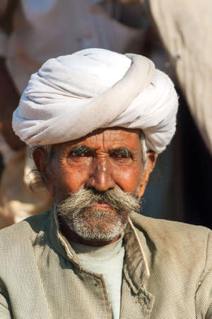 closeup cow face: NAGAUR, INDIA - FEBRUARY 10, 2011: An old cattle farmer with white turban looks into the camera. He
