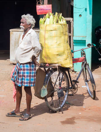 KUMBAKONAM, INDIA - OCTOBER 11, 2013: A man, street vendor, sells corn on the cob out of a yellow plastic bag fixed on his bike.