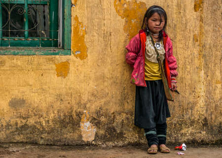 CAT CAT, VIETNAM - MARCH 10, 2012: A young Hmong schoolgirl in pink vest and black trousers stands against a filthy yellow school wall.