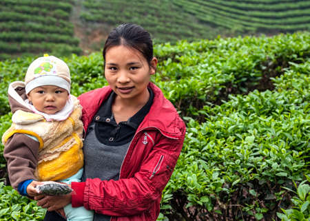 BAC HA, VIETNAM - MARCH 11, 2012: A young mother holds her baby in her arms, standing in the middle of a tea plantation.