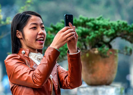 HANOI, VIETNAM - MARCH 6, 2012: A young Vietnamese woman wearing a leather vest takes a picture with her smart phone.