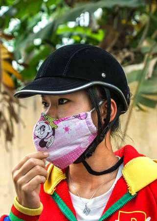 VAN LA, VIETNAM - MARCH 16, 2012:  Close up of a young Vietnamese women who covers her face with a Mickey Mouse face covering mask. Editorial