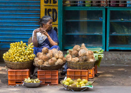 KUMBAKONAM, INDIA - OCTOBER 11, 2013: Graying female street vendor in blue sari sells coconuts, bananas and other fruits out of baskets in the street. Editorial