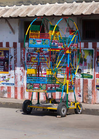 KUMBAKONAM, INDIA - OCTOBER 11, 2013: Small ferris wheel, aimed at little children, and only having four seats, stands in the street. Used at street fairs.